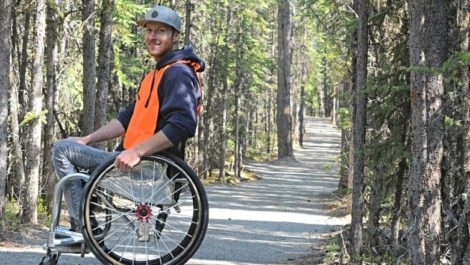 man in wheelchair on trail in woods