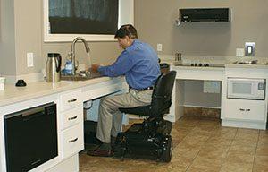 man in motorized chair at kitchen sink