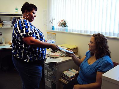 woman standing handing woman sitting informational materials