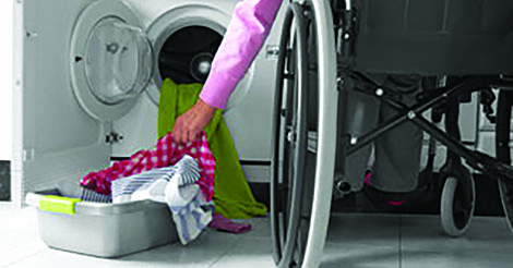 person in a wheelchair doing laundry