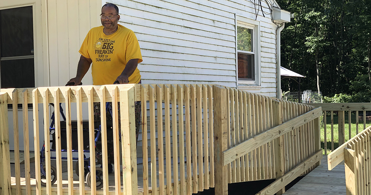 Man on newly built ramp to his home