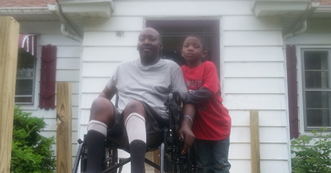 man in wheelchair with child outside their home
