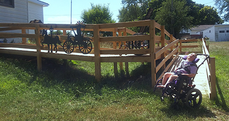 young girl in a wheelchair next to a ramp to her home