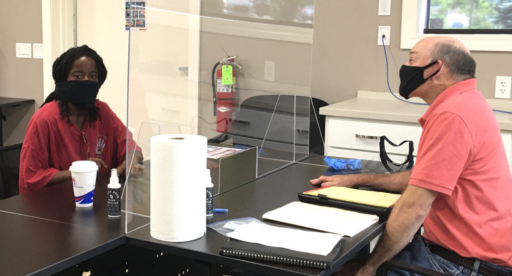 staff meeting with customer through plexiglass with masks