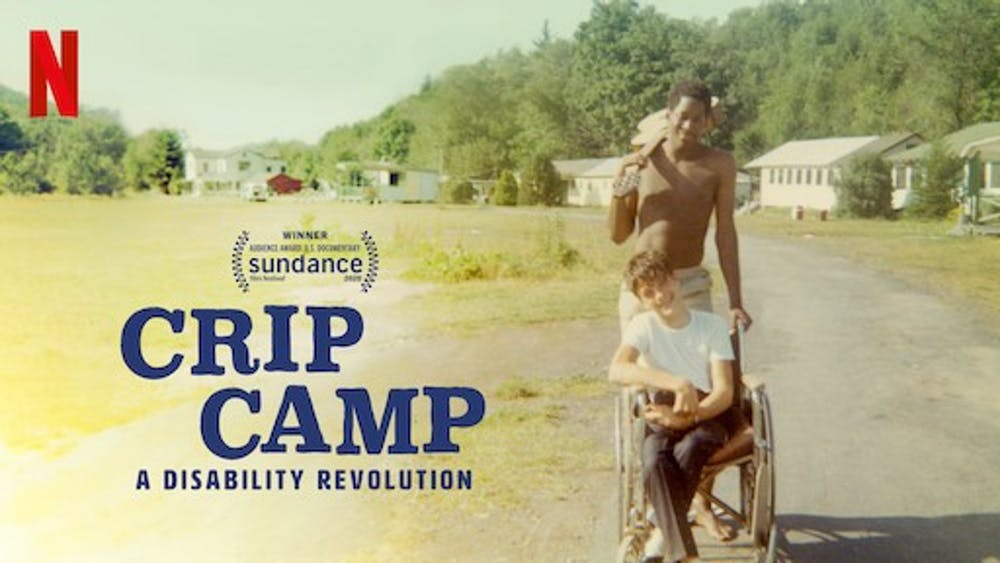 """""""Crip Camp"""" 2 young men, one pushing he other in a wheelchair outdoors"""